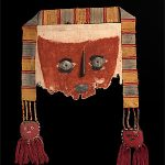 CHIMÚ culture North 1100 – 1470 AD Mask with trophy head pendants [Burial mask of woven cotton with a design of a human face, and a stuffed trophy head pendant on each side] 1279–1391 AD cotton, wool, copper, tin, wood, pigments, corn , woven, appliqué  80.0 (h) x 58.0 (w) x 7.0 (d) cm  43 National Gallery of Australia, Canberra NGA 1985.1829 Max Ernst Collection, purchased 1985