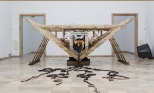 Matthew Barney, Boat of Ra, (2014), wood, resin-bonded sand, steel, furniture, cast bronze and gold-plated bronze, 335.3 x 1524 x 731.5cm. Courtesy of the artist and Gladstone Gallery, New York and Brussels