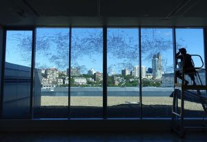 Gosia Wlodarczak drawing directly onto a window in the AGNSW, overlooking the landscape of Woolloomooloo