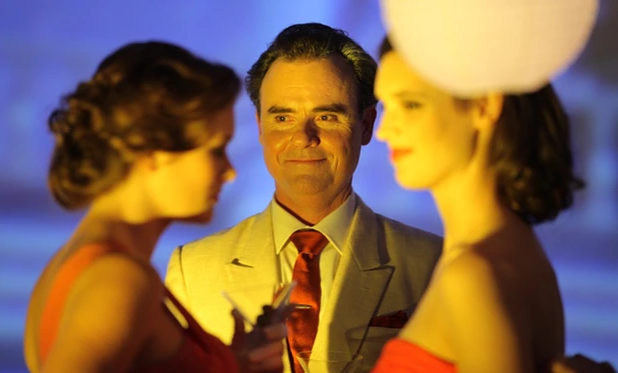 Orry-Kelly played by Darren Gilshenan with cocktail party guests in 'Women He's Undressed' (2015)